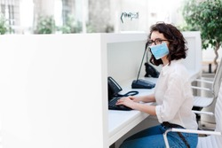 Receptionist wearing protective mask at reception in hotel. Protection employees on workplace. Young woman working in office. Social distancing during quarantine, staff safety.