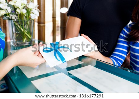 Receptionist woman gives gift certificate to young couple for visit spa salon. #1316177291