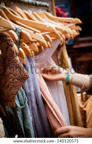 Recession bargains: rack of second-hand dresses for sale at market. Portrait orientation.