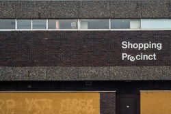 Recession Image Of A 1970s Style Grim Urban Rundown British Shopping Precinct Sign