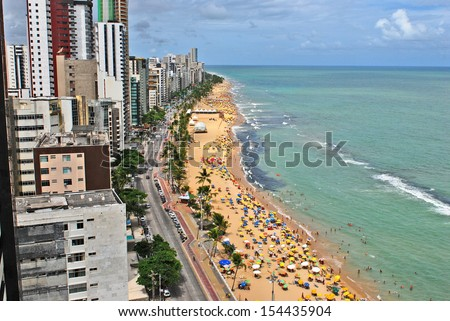 Recife, Pernambuco, Brazil, 2009. A view to the city beach with lots of Brazilian people sunbathing and swimming, and umbrellas, a view from the top of a skyscraper. Foto stock ©