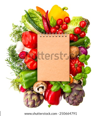 recipe book with fresh organic vegetables and herbs isolated on white background. healthy food ingredients