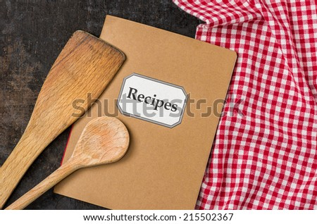 Recipe book with wooden spoons on a red checkered tablecloth