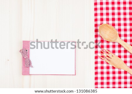 Recipe cookbook, fork, spoon, checkered tablecloth on wood background