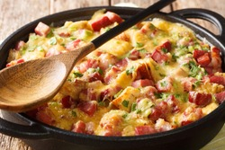 recipe for a simple strata with ham, bread, onions, cheese and eggs close-up in a pan on the table. horizontal