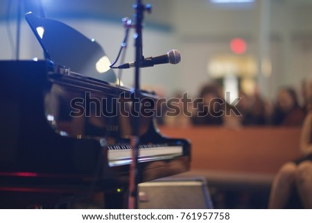 Shutterstock Recital Music Performance large venue with Grand Piano and microphone. Shot from back of stage.