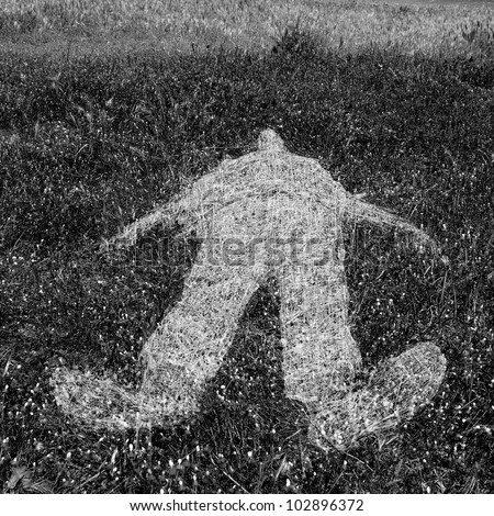 Reclining human figure outline imprinted on grass. Black and white.