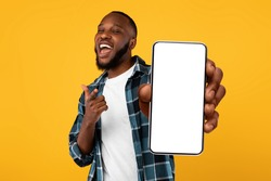 Recommendation. Portrait of excited black guy holding big smartphone with white blank screen in hand, showing close to camera and pointing at device. Gadget with empty free space for mock up, banner