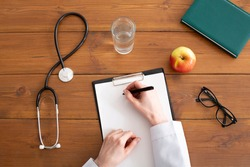 Recommendations and prescription from doctor. Woman in white coat writes on tablet at workplace, on wooden table with stethoscope, glasses, apple and glass of water, top view, copy space, cropped