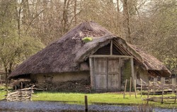 Reconstruction Of A Bronze Age Roundhouse With Thatched Roof And Doors Closed On The Edge Of A Flooded Marsh. Taken at Testwood Lakes, UK, Where Two Of The Oldest Bridges Were Found In Britain.