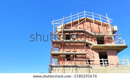 Reconstruction of block of houses with scaffoldingScaffold before house. Reconstruction work using scaffolding. Composition for building company. Symbol of construction
