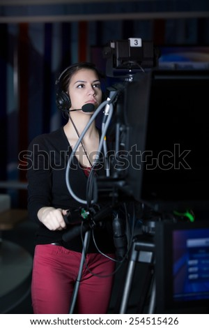Recording at TV studio.Professional camera operator with headphones and camera in television news broadcast.Camerawoman working with big broadcasting camera.Positioned video camera.Behind the scenes