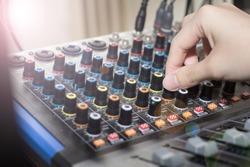 Recording engineer's hand adjusts volume on audio sound board, Turning a dial on a mixing board