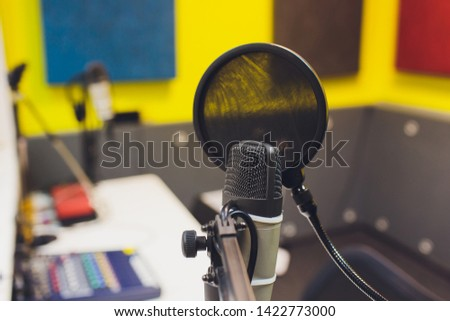 Recording equipment in studio. Studio microphone with headphones and mixer background. Elevated view.