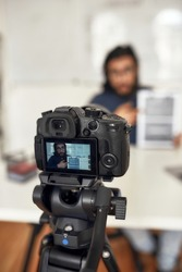 Recording video blog. Young man teaching online, explaining new theme while working from home. Focus on camera, professional digital equipment. E-learning. Distance education. Blogging, vlogging
