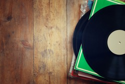 records stack with record on top over wooden table. vintage filtered