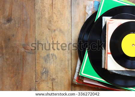 records stack with record on top over wooden table. vintage filtered\n