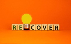 Recover concept. Wooden cubes with word 'recover'. Yellow light bulb. Beautiful orange background. Business and recover concept. Copy space.