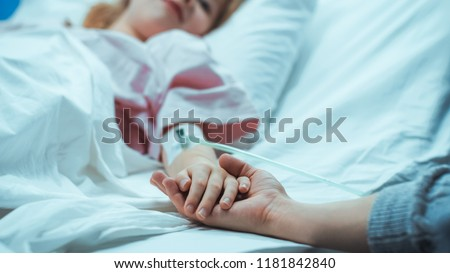 Recovering Little Child Lying in the Hospital Bed Sleeping, Her Hand Falls into Mother's and She Holds it Comfortingly. Focus on the Hands. Emotional Family Moment.