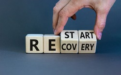 Recovery and restart symbol. Businessman hand turns cubes and changes the word 'recovery' to 'restart'. Beautiful grey background. Business and recovery - restart concept. Copy space.