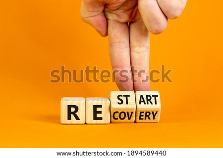 Recovery and restart symbol. Businessman hand turns cubes and changes the word 'recovery' to 'restart'. Beautiful orange background. Business and recovery - restart concept. Copy space. Foto stock ©