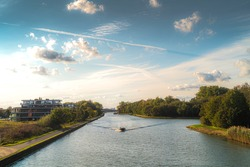 recreation and pleasure at canal roeselare leie envirement of izegem ingelmunster in flanders.  Toerism in flanders, boat for leisure.  Beautifull view in unknown area.  Beautifull sky combined w boat