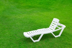 Recreation and tourism advertising. Empty white plastic chair or chaise longue, on the green grass of a fresh lawn. Place for text