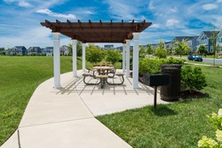 recreation area with pergola and barbecue in a residential area. flowers and green lawn under the blue sky.