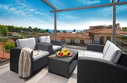 Recreation concept panorama of modern patio with wicker grey rattan furniture. Contemporary armchairs, couch, table on roof top terrace of luxury sea view resort in old European city
