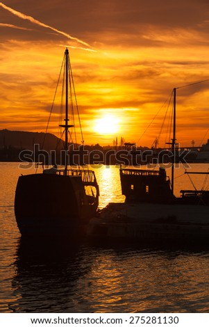 Recreation sailing ships stand moored in Varna port at the sunset. Bulgaria, vertical photo
