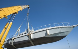 Recreational boat being lifted by heavy industrial crane machinery against blue sky background