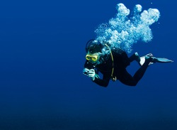 Recreational scuba diver with yellow mask, cloud of bubbles in black neoprene suit taking underwater photo in deep blue water of Red Sea with great visibility