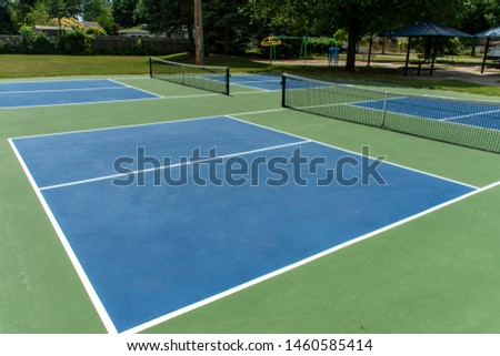 Recreational sport of pickleball court in Michigan, USA looking at an empty blue and green new court at a outdoor park. #1460585414