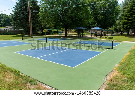 Recreational sport of pickleball court in Michigan, USA looking at an empty blue and green new court at a outdoor park. #1460585420
