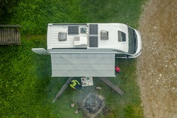 Recreational Vehicle Campground RV Park Pitch with Modern Camper Van Equipped with Solar Panels and Campfire Place Aerial View. Outdoor Weekend Getaway