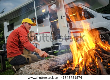 Recreational Vehicle RV Camper Camping and Family Time. Caucasian Father and His Daughter Hanging Next to Campfire on Their RV Park Pitch. Class C Motorhome in Background.