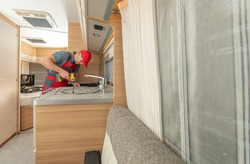 Recreational Vehicles Caucasian RV Technician in His 40s Repair Modern Travel Trailer Stove. RV Appliances Industry.