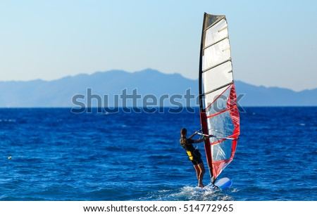 Recreational Water Sports. Windsurfing. Windsurfer Surfing The Wind On Waves In Ocean, Sea. Extreme Sport Action. Recreational Sporting Activity. Healthy Active Lifestyle. Summer Fun Adventure. Hobby