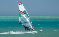 Recreational water sports: windsurfing. Windsurfer surfing waves in the sea on a windy day. Extreme sports action with wind and water. Recreational sporting activity. Healthy active lifestyle