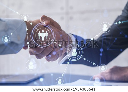 Recruitment concept to hiring of a new talented specialists for international company. Handshake to sign in of employment agreement. Social media hologram icons over the table with documents. Сток-фото ©