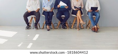 Recruitment process and office paperwork concepts. Low section crop of group of job candidates waiting in line for interview. Company workers with documents sitting in queue on chairs Photo stock ©