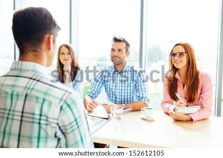 Recruitment. Three corporate people Interview young man