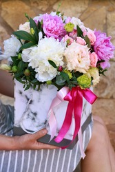 rectangular box with flowers on the girl's lap, close-up with a blurry background. box with ribbons, with peonies, roses, eustoms, as a gift for Valentine day