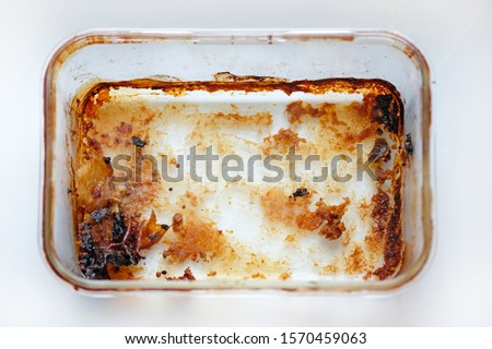 Rectangular glass baking dish top view. Dirty meat baking dish. An empty tray made of heat resistant glass after baking meat.