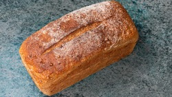 rectangular loaf of wheat bread with a baked shiny crust on the kitchen table