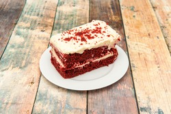 Rectangular portion of delicious red velvet cake with two layers of red sponge cake on a white round plate
