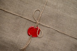 Rectangular recycled brown cloth parcel packaging tied with twine and sealed with red sealing wax, red sealing wax linen rope