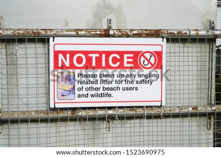 Rectangular red and white sign asks fishermen and beach users to clean up litter, warning of the danger of fish hooks and angling rubbish to wildlife. The notice is attached to a metal and mesh fence.