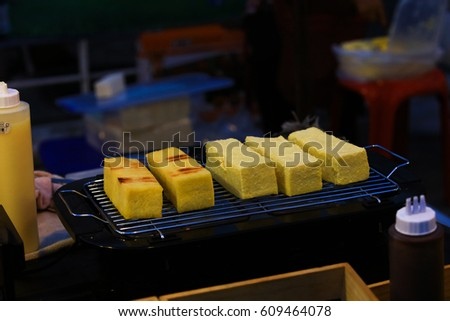 Rectangular rod Toast with yellow butter selling at local market , toasting the bar bread on heater Electric grill #609464078