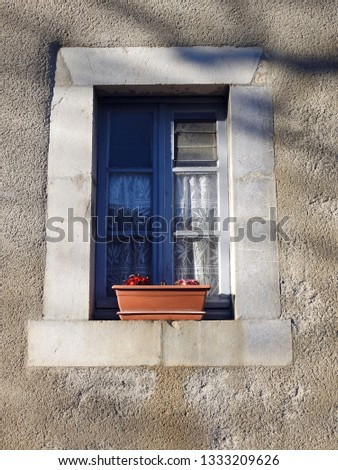 Rectangular vintage wooden window with embroidered curtain, heavy blocks/bricks frame and flower box, centered in exterior wall of building in rural France